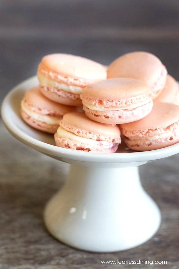 a cake stand full of raspberry macarons