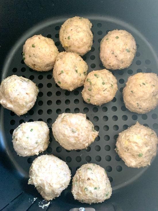 cooked ground chicken meatballs in an air fryer basket