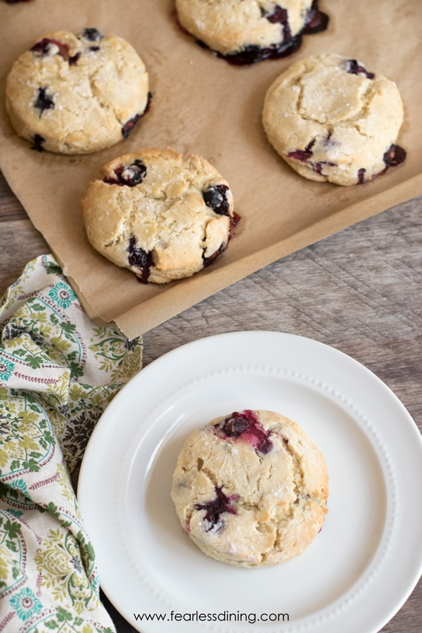 top view of a gluten free blueberry scone on a plate with the pan behind the plate