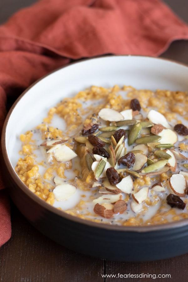 a bowl of gluten free pumpkin steel cut oats topped with pumpkin seeds, almonds and raisins