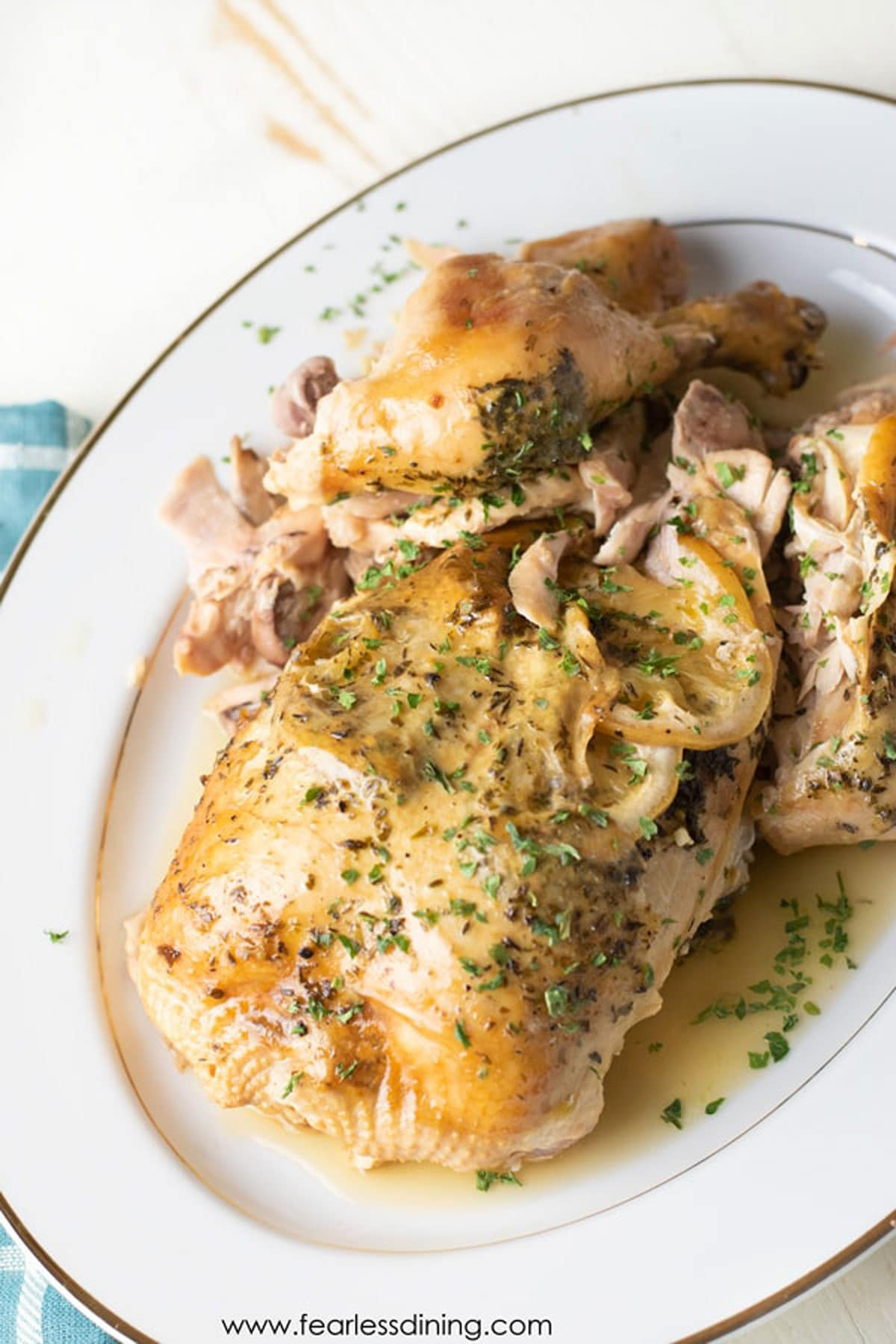 a platter with a whole slow cooked lemon chicken