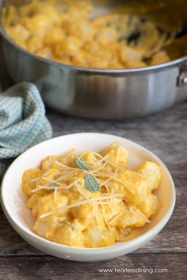 a bowl of cauliflower gnocchi topped with pumpkin alfredo sauce