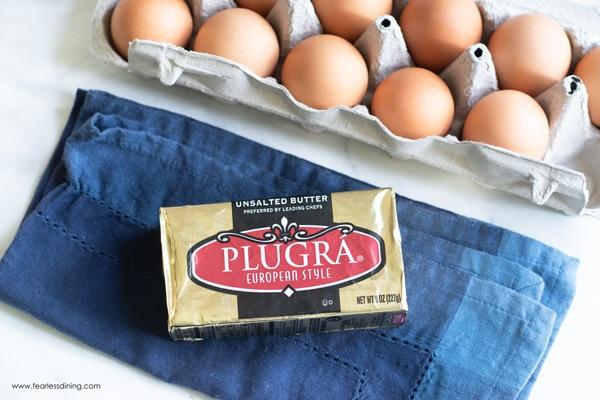 butter with a dozen eggs on a blue napkin
