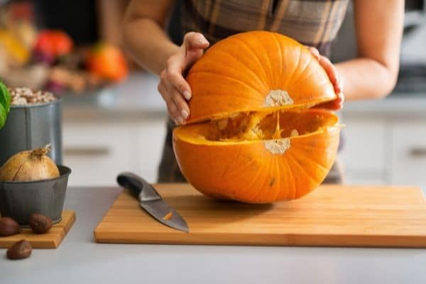 cutting a pumpkin in half and lifting part to separate it