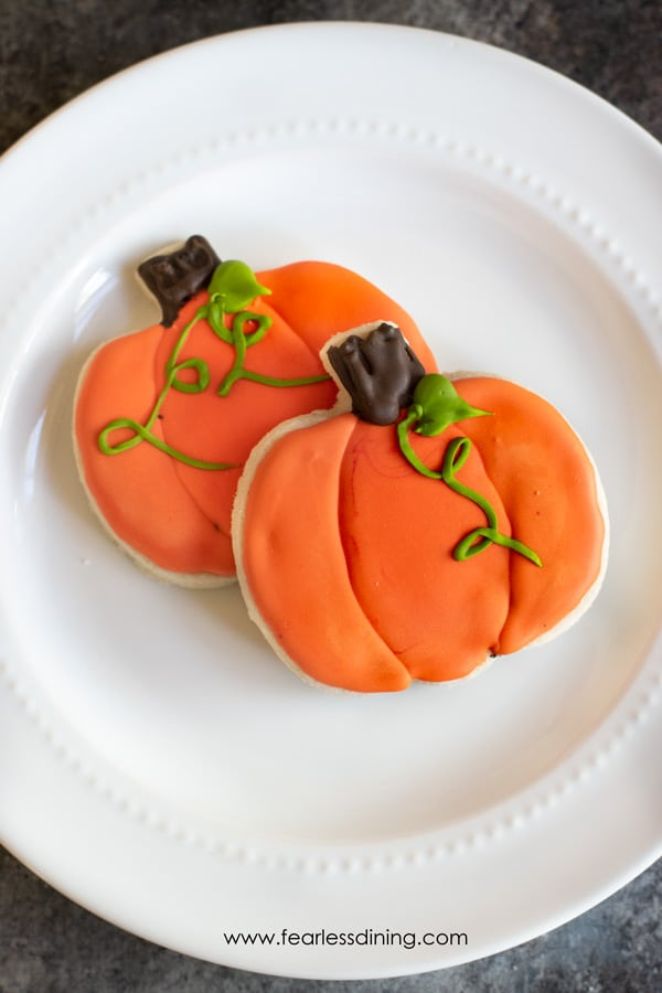 two gluten free halloween cut out cookies on a plate. They are decorated pumpkin shaped sugar cookies