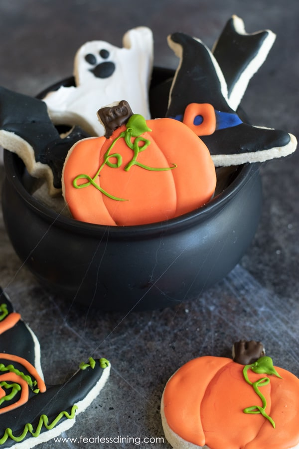 a cauldron filled with gluten free Halloween cut out cookies