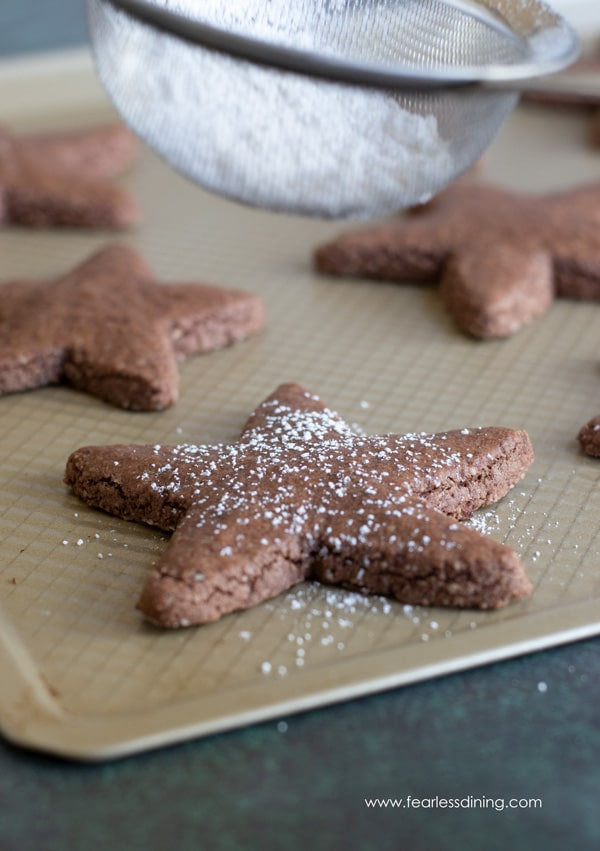 dusting powdered sugar onto gluten free Swiss brunsli cookies