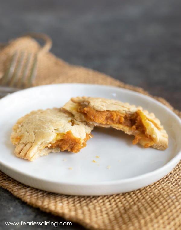 a gluten free pumpkin hand pie cut in half on a plate