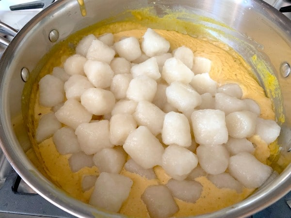 adding the cooked gnocchi to the pan with pumpkin alfredo sauce