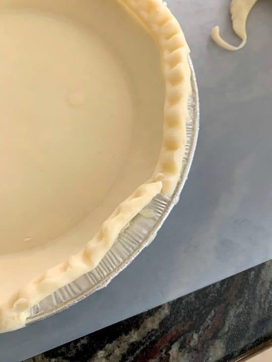 peeling a premade gluten free pie crust out of the tin