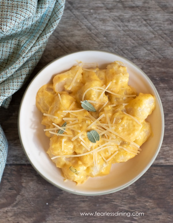 a bowl full of cauliflower gnocchi topped with a pumpkin alfredo sauce