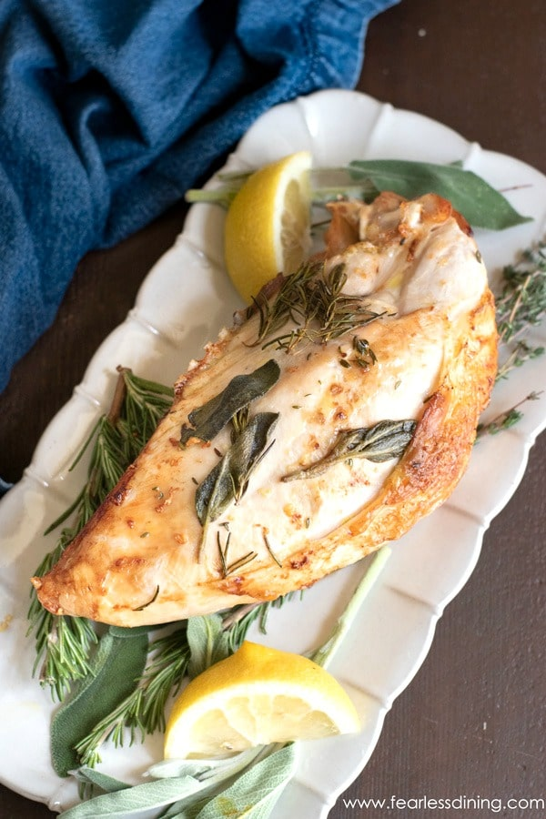 a turkey breast on a platter with fresh herbs