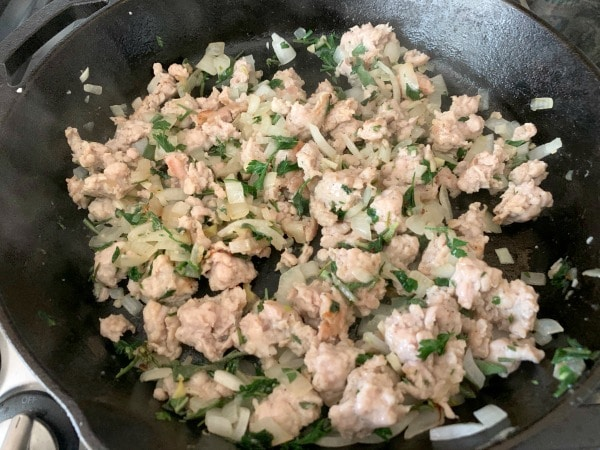 cooked sausage, onion and herbs in a pan