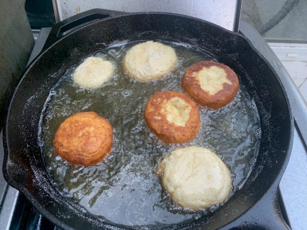 frying donuts in hot oil in a cast iron skillet