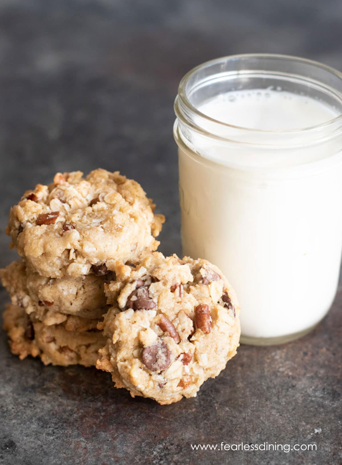 a stack of cowboy cookies next to a glass of milk