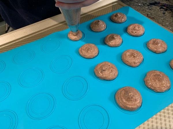 piping the macaron batter onto the macaron mat
