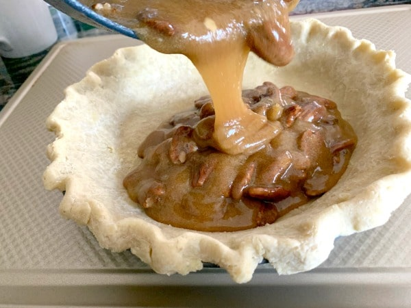 pouring pecan pie filling into the crust