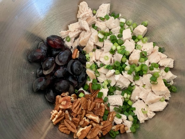 chopped cooked chicken, grapes, pecans, and scallions in a bowl