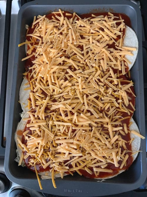casserole is topped with enchilada sauce and dairy-free cheddar cheese