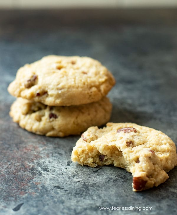 a stack of gluten free butter pecan cookies. One cookie has a bite taken out.