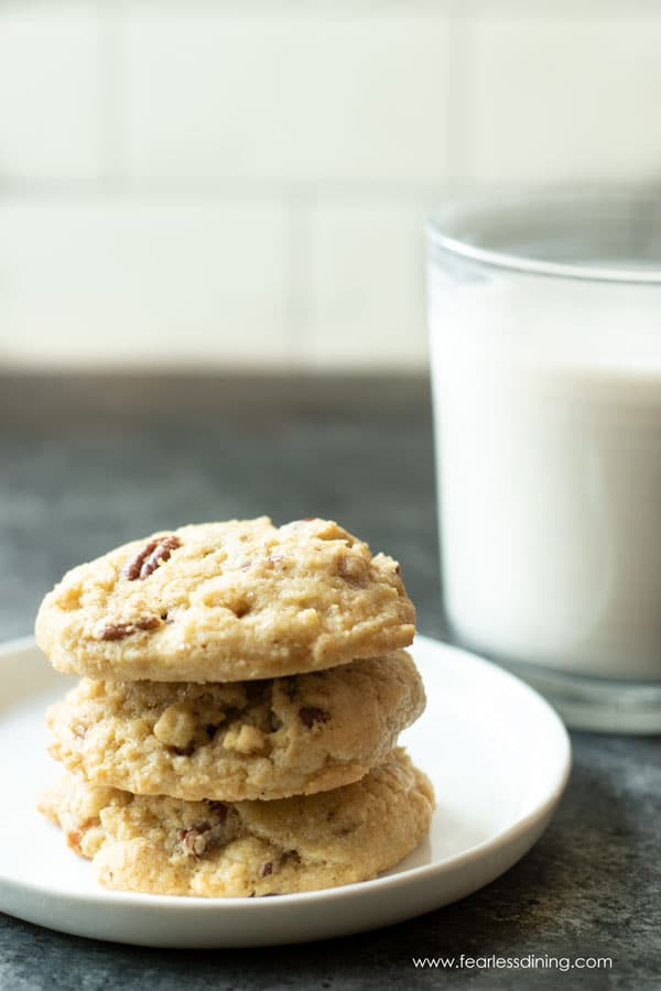 a stack of gluten free butter pecan cookies next to a glass of milk
