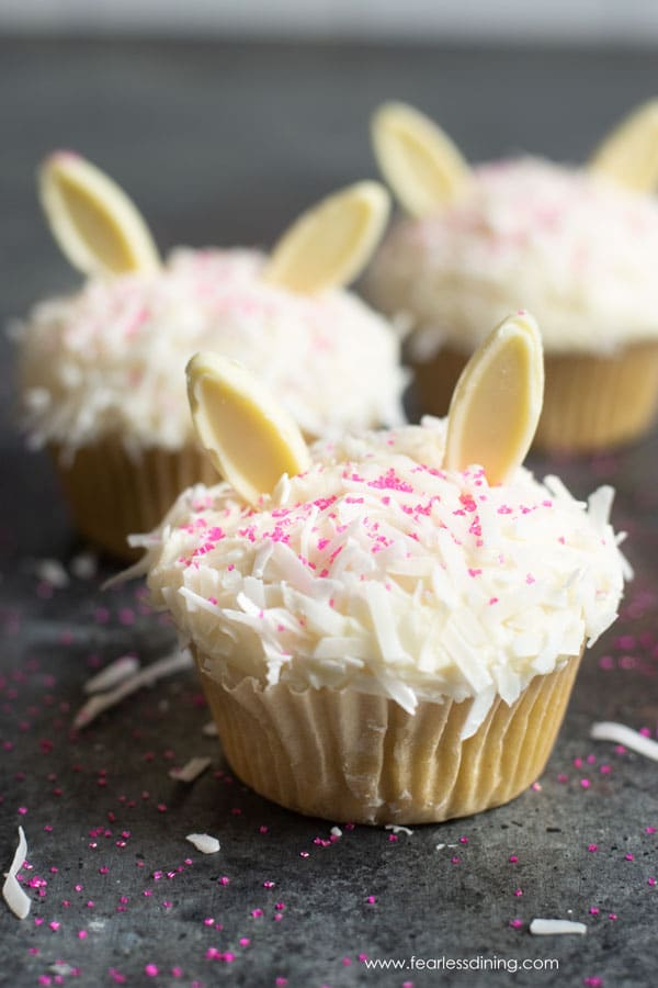 gluten free coconut cupcakes with white chocolate bunny ears and they are dusted with hot pink sprinkles.