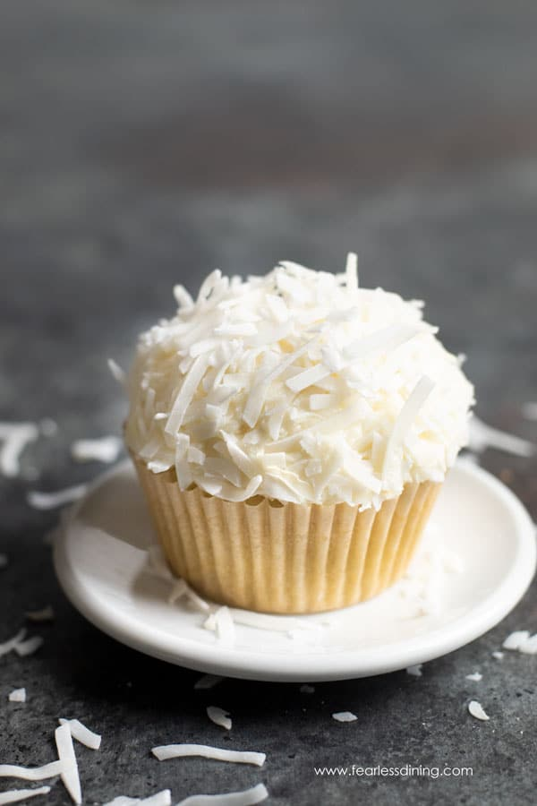 a single gluten free coconut cupcake on a white plate