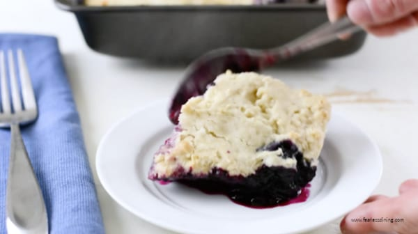 spooning a serving of cobbler on a small plate