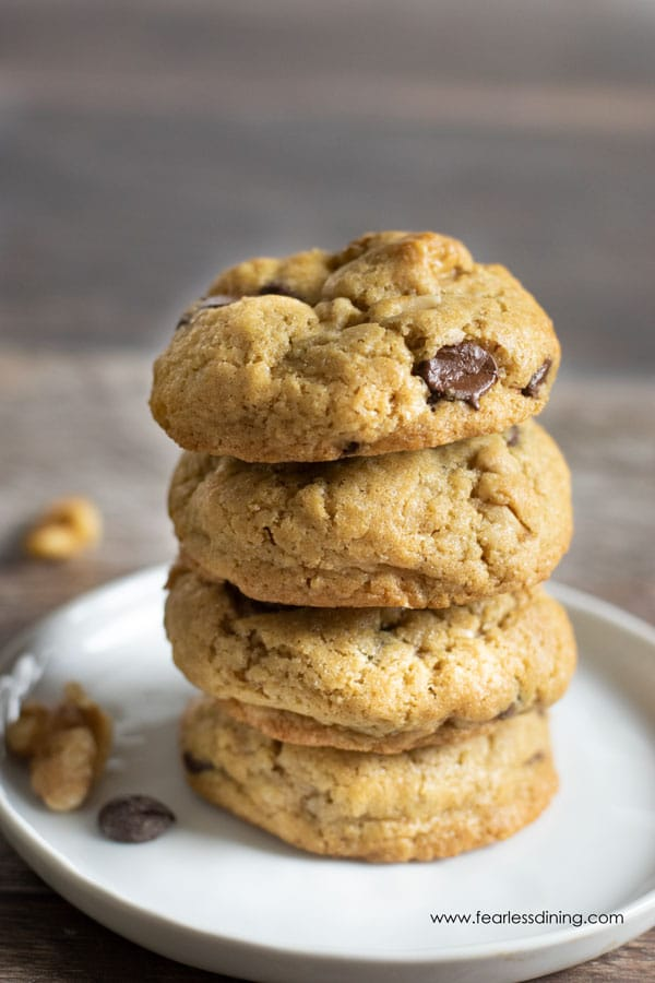 A stack of gluten free chocolate chip walnut cookies. The stack is on a white plate with walnuts and chocolate chips next to it.