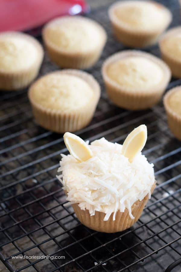frosting gluten free coconut cupcakes on a rack.