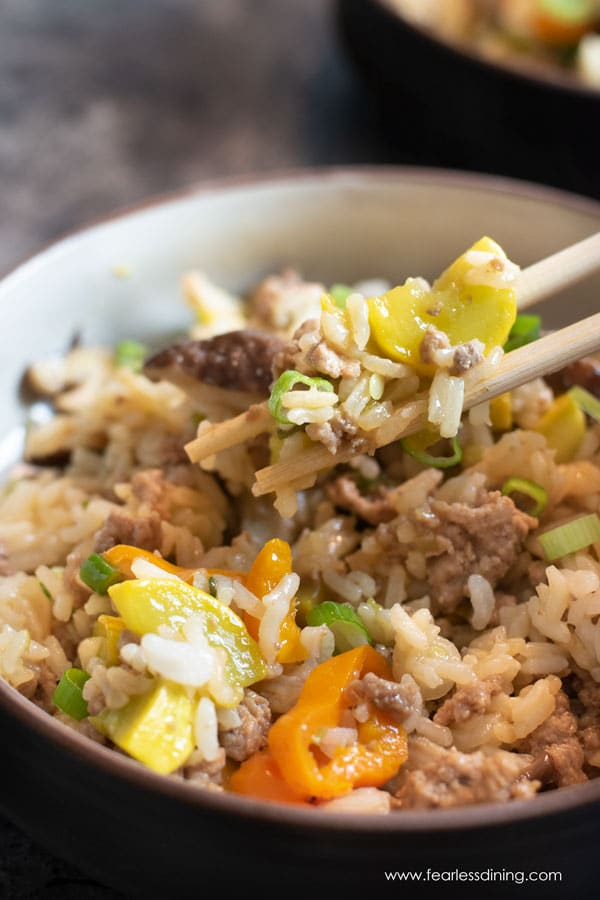 a pair of chopsticks lifting some fried rice