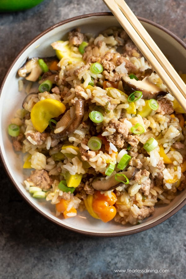a top view of a bowl of gluten free ground pork fried rice. Chopsticks are sitting on the rim of the bowl