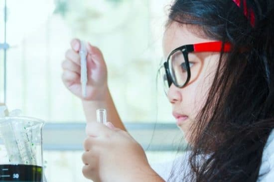a child doing a science experiment with a test tube