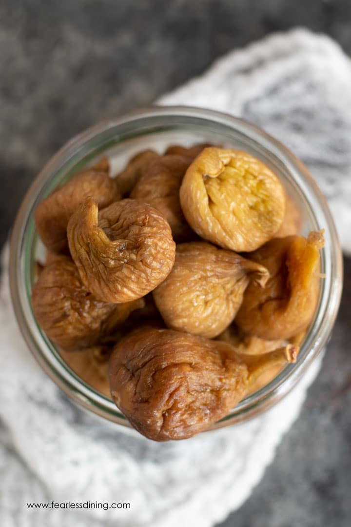 A top down view of a jar filled with dried golden figs.