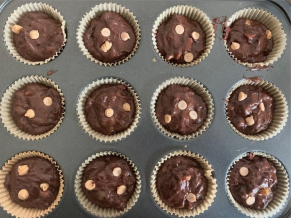 Muffin cups filled with batter ready to bake