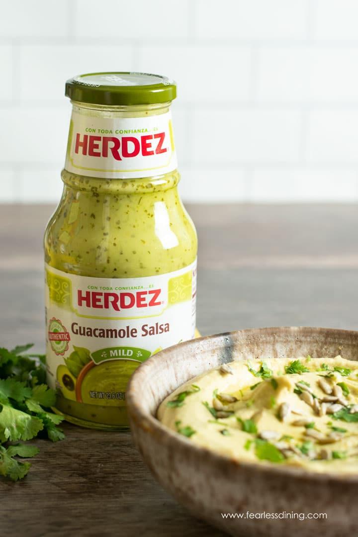 a jar of Herdez guacamole salsa next to a bowl of guacamole hummus.