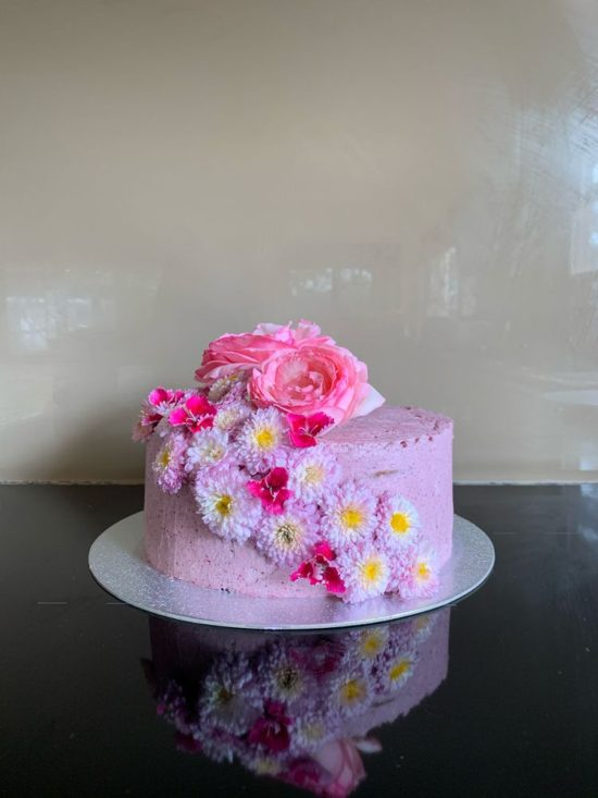 Leah W sent a photo of this cake with pink frosting and decorated with fresh pin and purple flowers.