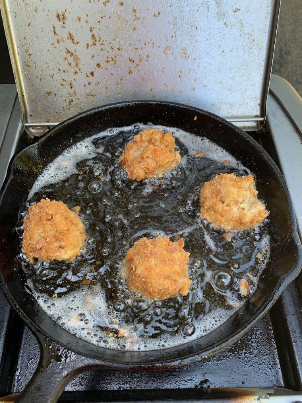 macaroni and cheese balls frying in oil in a cast-iron pan