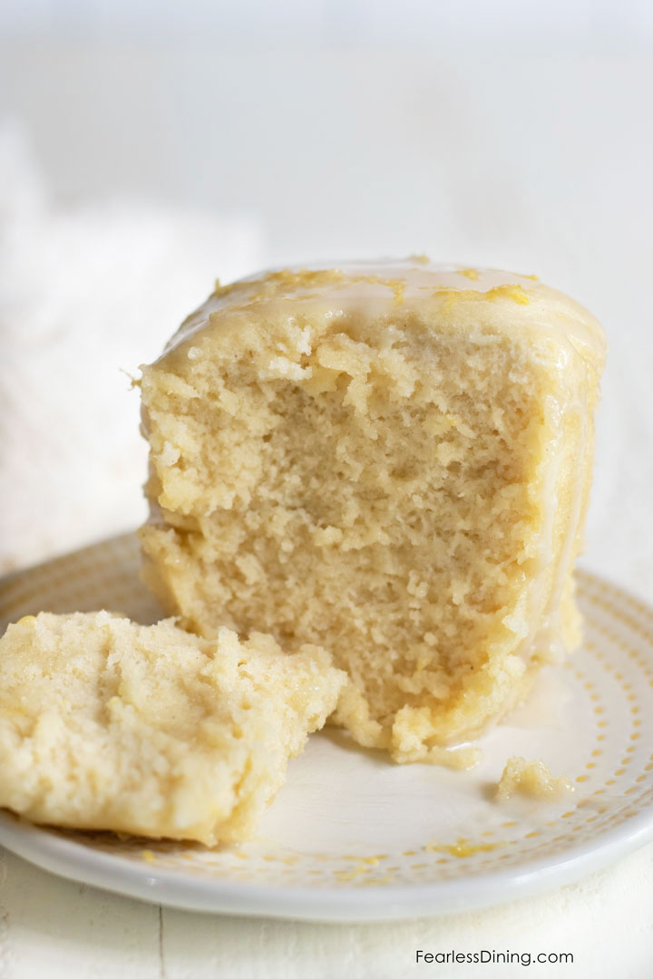 A gluten free lemon mug cake on a small pate. The cake is cut in half so you can see the inside of the cake