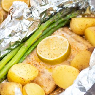 cooked mahi mahi filet with asparagus and potatoes in a foil packet