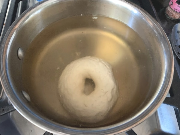 an uncooked bagel in a pot of boiling maple syrup water.