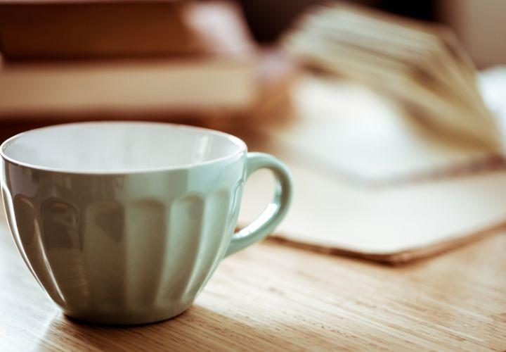 an empty pale green coffee mug near an open book