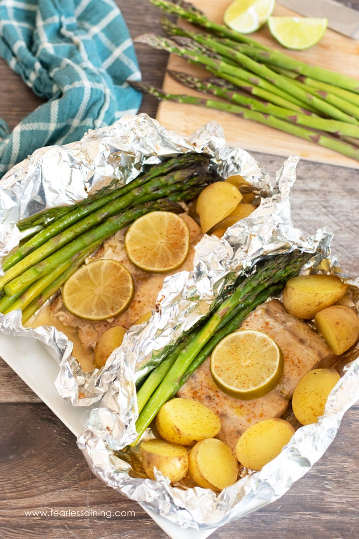 two foil packets with mahi mahi and vegetables