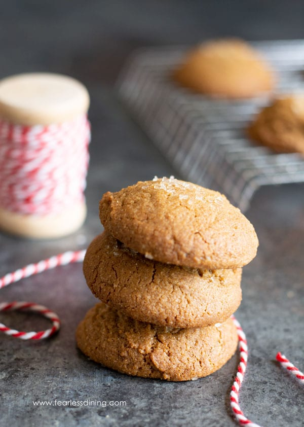 a stack of ginger cookies next to a rack of cookies