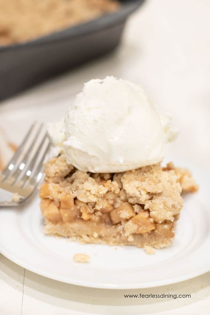A gluten free apple crumble bar on a white plate topped with a scoop of vanilla ice cream