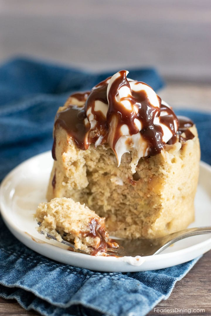 a fork full of cake is sitting next to the mug cake. You can see the fudge dripping down the cake where the fork cut in.