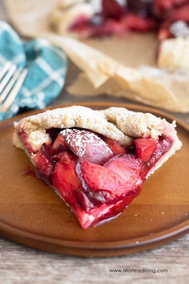 a front on view of a slice of plum galette on a wooden plate.