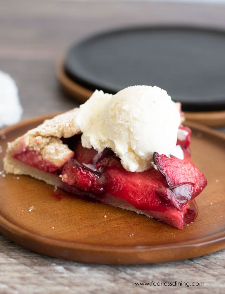 a slice of plum galette with a  scoop of vanilla ice cream on top