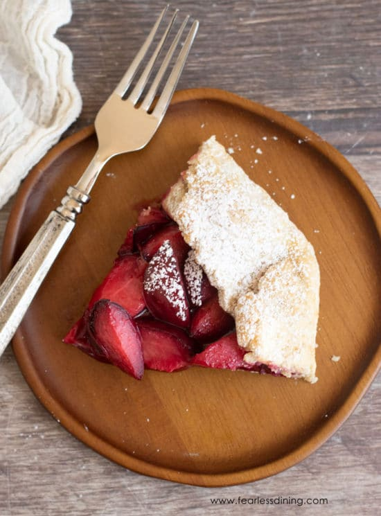 Top close up view of a slice of plum galette with a fork.