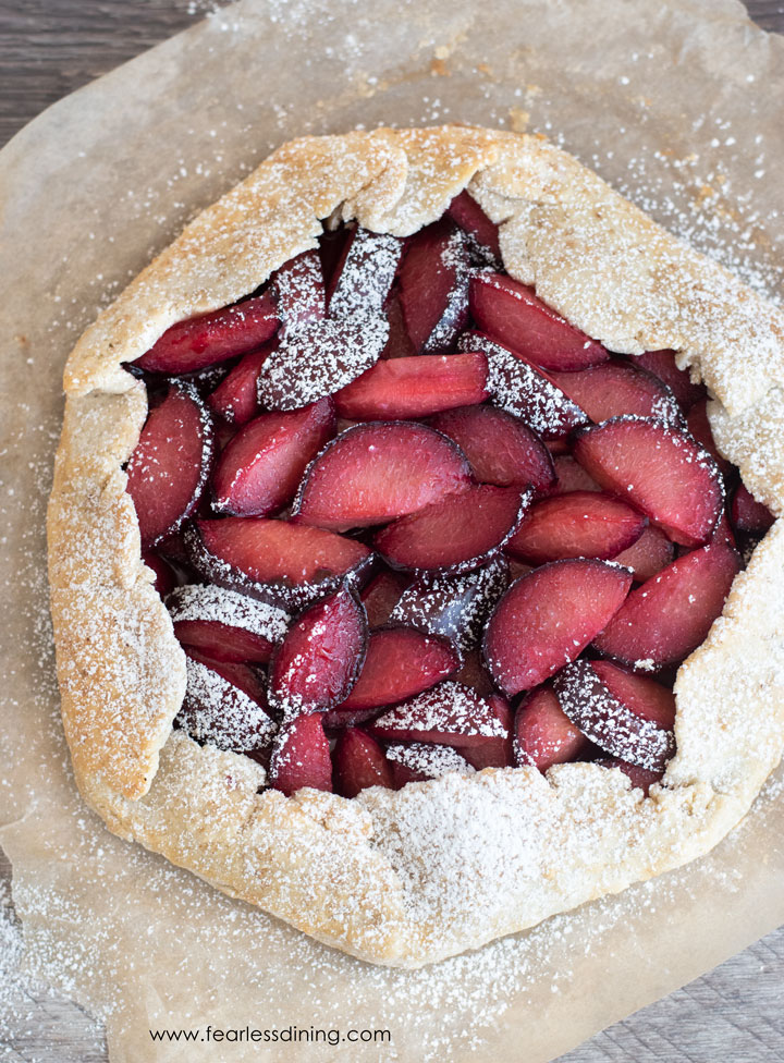 The top view of a whole gluten free plum galette on a piece of parchment paper.